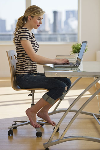 young woman using her computer on her desk while seated in her chair